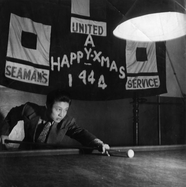 A Chinese-American member of the United Seaman's Service plays pool or snooker at the London club during Christmas, 1944. The USS was founded in 1942 to promote the welfare of American seafarers and their dependents, seafarers of all nations