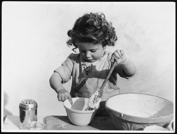 A little girl plays with the cake mix with a wooden spoon