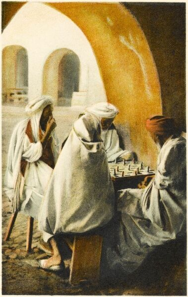 Four Algerian men playing chess in a shady section of a secluded courtyard