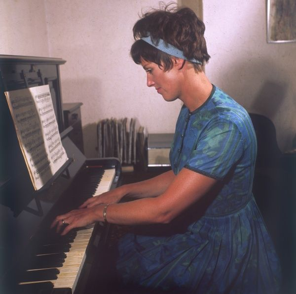 A young woman plays an upright piano, reading sheet music. Date: 1969