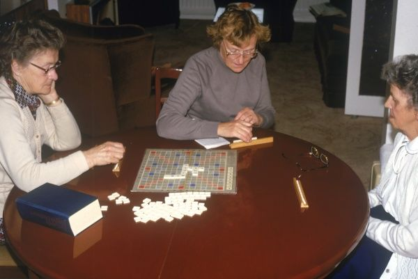 Three women playing the word conundrum game 'Scrabble'. Date: 1970s