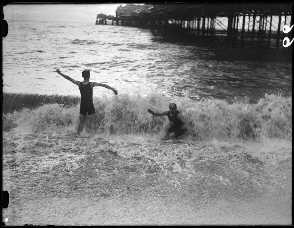 A man and a boy enjoy an exhilirating splash in the cold surf at Brighton, Sussex, England