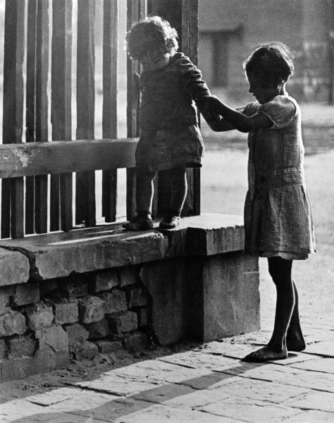 An older little girl helps a younger one, her sister, perhaps, to walk on a wall. Date: 1930s
