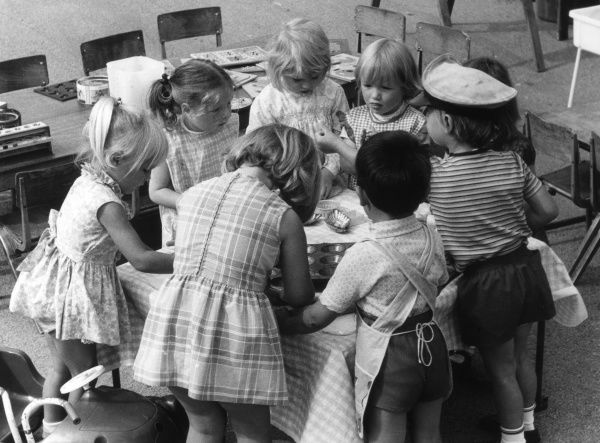 Children, mostly little girls, around a circular table at a British playschool. Date: 1960s