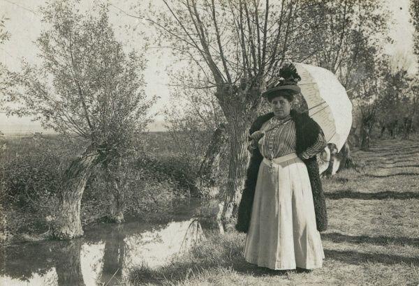 A plump, middle aged woman with an open parasol, standing by a stream in the countryside. Date: early 20th century