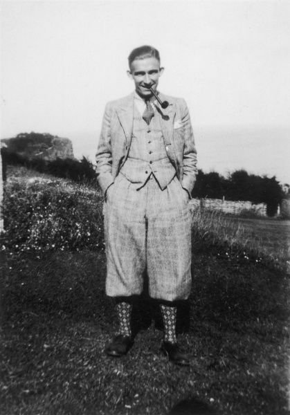 A gentleman wears a window- pane check suit of PLUS-FOURS, waistcoat & jacket with Argyll socks, as he stands, smoking his pipe, in the garden of 'Harrowcliffe', Teignmouth