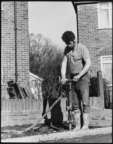 A man with curly dark hair using a pneumatic drill to dig up an old pavement