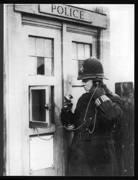 A police constable using the telephone at a police box