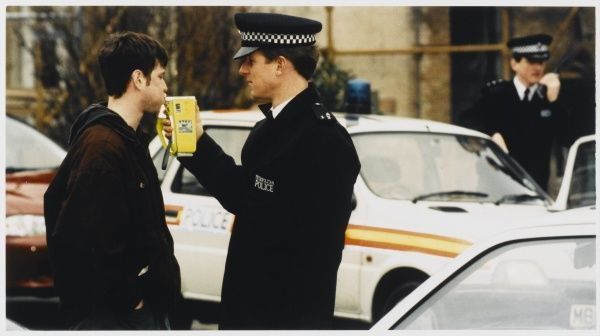 Policeman testing a man for alcohol with a breathaliser in the street Metropolitan Police
