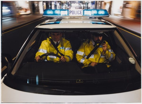 Police officers driving a police car during a car chase, on the radio and wearing seatbelts. Metropolitan Police on an emergency call