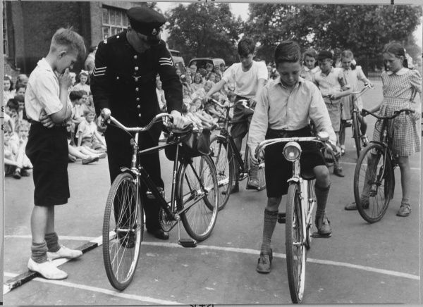 Metropolitan Police officer from the Road Safety Unit carrying out a cycling proficiency course for children on bicycles at a school