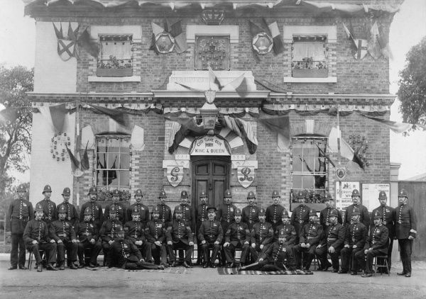 A group of policemen pose for their photograph outside Hammersmith Police Station, west London, to commemorate the Coronation of King George V. Many flags decorate the building, and a sign over the main doorway reads God Save Our King & Queen