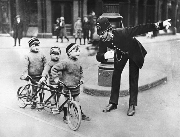 Police officer giving directions to three boys with a three person bicycle pointing in the opposite direction Transport