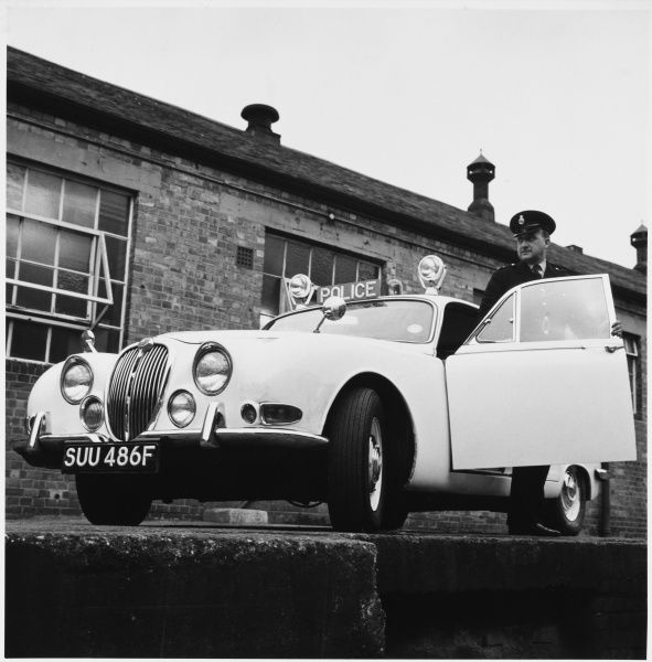 A police officer emerges from his rather smart 1968 S-type Jaguar police car, equipped with police sign and flashing lights on the roof