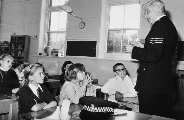 Police officer talking to schoolchildren in class at St Patrick's School, Wapping, London. Metropolitan Police