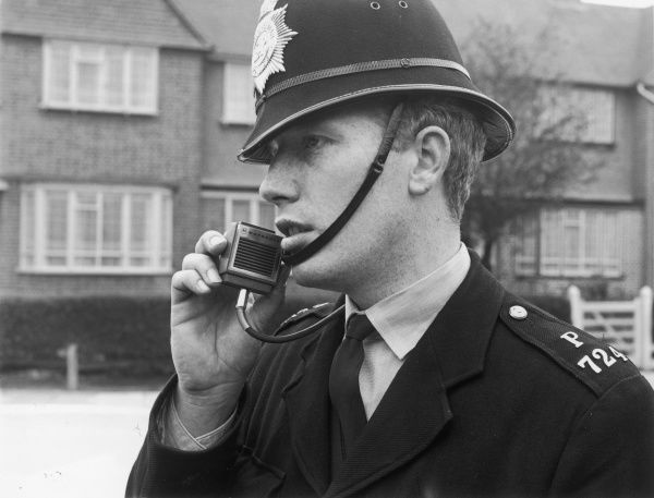A Metropolitan Police officer using a small walkie talkie radio made by Motorola on a London street