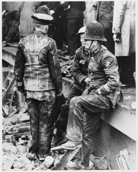 Dust-covered police officers help with the rescue effort in the bombed areas of London during World War II