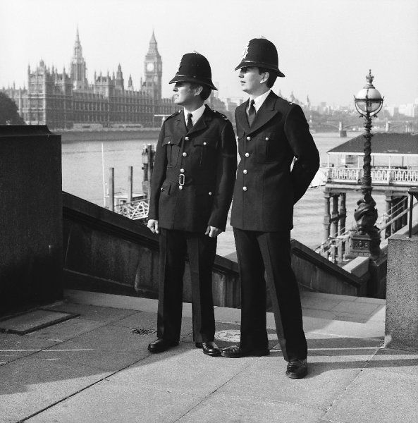 Police officers wearing old and new uniforms. On left wearing 1980 uniform, on right the old from the period 1959-1980 Metropolitan Police in London near Houses of Parliament