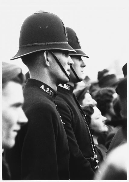 Two young British policemen, photographed in profile whilst on duty at a May Day rally