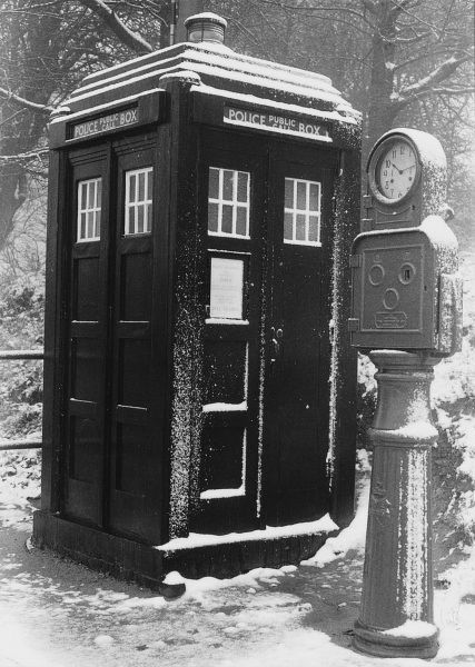A Police Public Call Box, on a London street on a snowy day. The Metropolitan Police introduced police boxes throughout the London area between 1928 and 1937. The one pictured is a Mackenzie Trench style police box, made famous by the long-running TV series