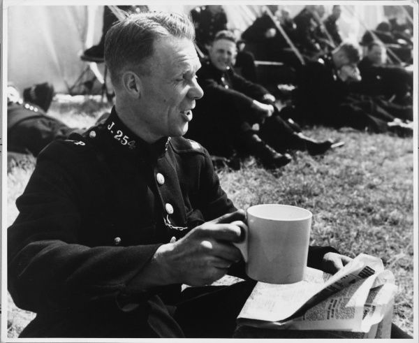 A Metropolitan Police officer drinking a cup of tea break on Derby Day. In 1947 over 16 million cups of tea were drunk by the Metropolitan Police