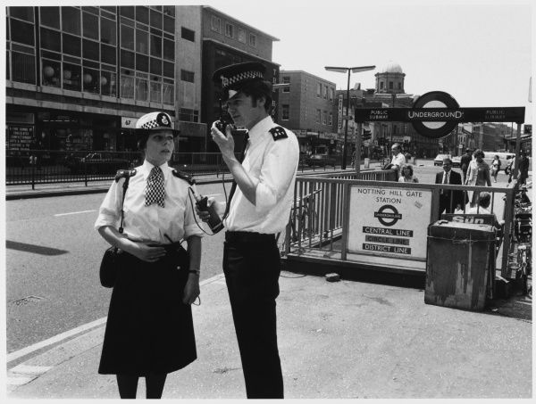 Police officers talking on a walkie talkie in the street at Notting Hill Underground Station, London Metropolitan Police
