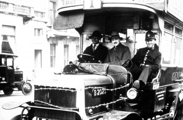 A policeman sitting alongside the driver on a London bus
