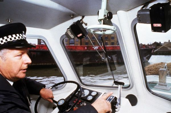 A policeman at the controls of a boat on the River Thames in London