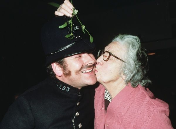 A policeman receives a kiss from an enthusiastic granny brandishing a bunch of mistletoe