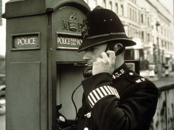 A policeman on the phone at a police public call box on a London street