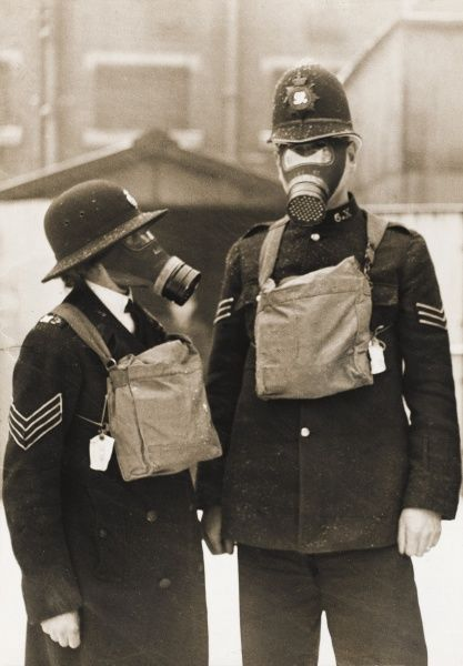A policeman and a policewoman wearing civilian gas masks outside Harrow Road Police Station (X Division) before the outbreak of World War Two. The respirator is contained in the canvas bag