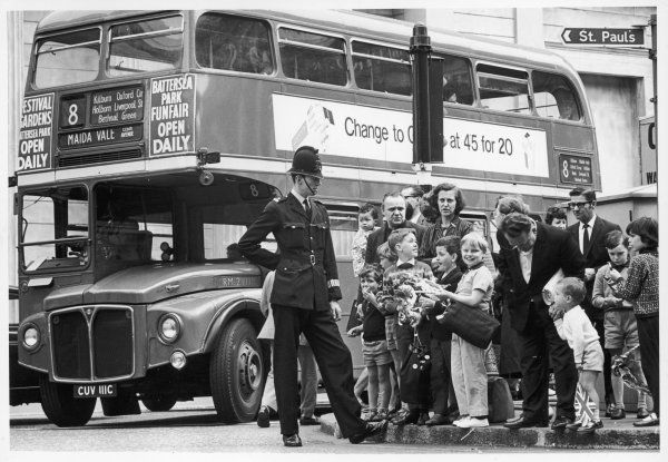 A policeman keeps his eye on a crowd of young sightseers, keeping them on the pavement and well out of the path of the No. 8 Routemaster bus to Maida Vale, London
