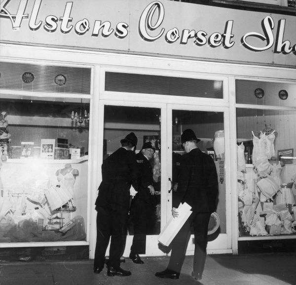 'Hello, hello', what are these three policemen doing outside a corset shop? Date: 1960s