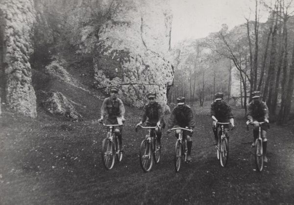 Five Polish Scouts on bicycles cycle next to a cliff in the countryside. 1930s