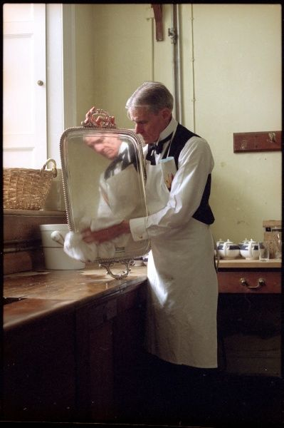 An Edwardian butler polishes a silver tray until he can see his face in it