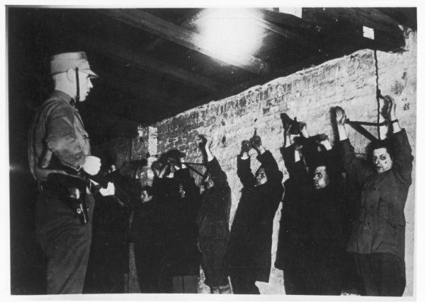 Political prisoners with raised arms are lined up against a wall at gunpoint and held by the SA