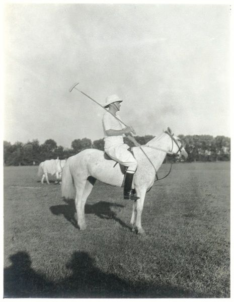 Side view of a polo player on his pony, with his polo stick resting on his shoulder and a pith helmet on his head