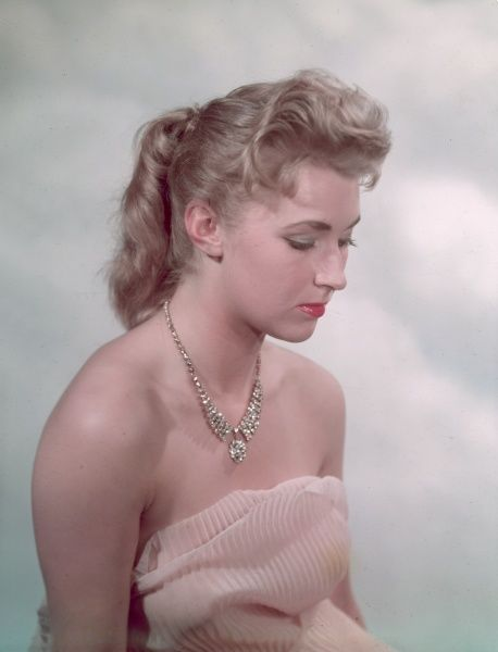 A blonde girl, with a fifties ponytail, models a diamante necklace