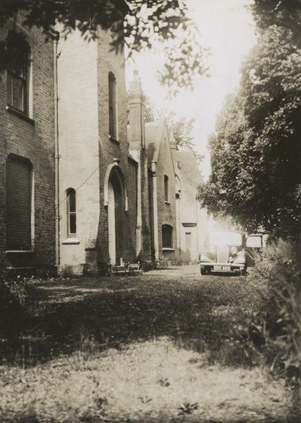 "Undated photograph of front and porch entrance to Borley Rectory from the drive. The bricked up window of the dining room can be seen on left, done on account of alleged annoyance by the ""nun"". HPG/1/3/3 (vii)&quot"