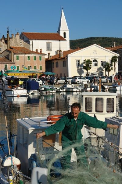 View of the port and town of Izola, Slovenia, with a fisherman working in the foreground