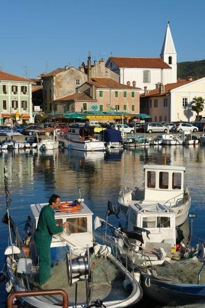 View of the port and town of Izola, Slovenia, with a fisherman on a boat in the foreground