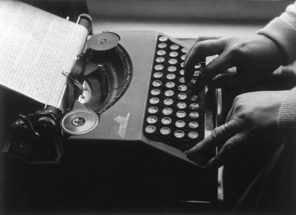 A portable typewriter in action. Date: circa 1950