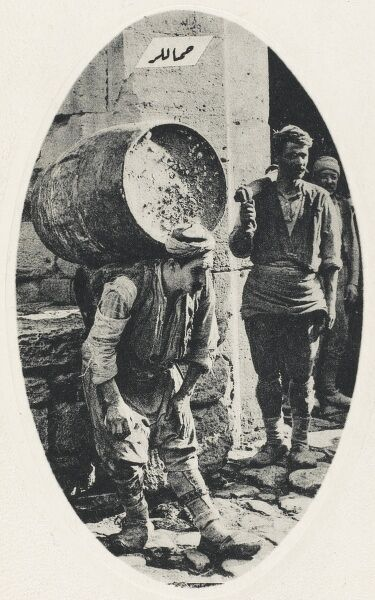 A Porter bends his back to carry a heavy barrel - Constantinople, Turkey