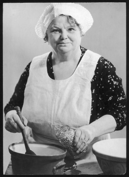 A portly woman adds beans to a casserole. Date: 1930s
