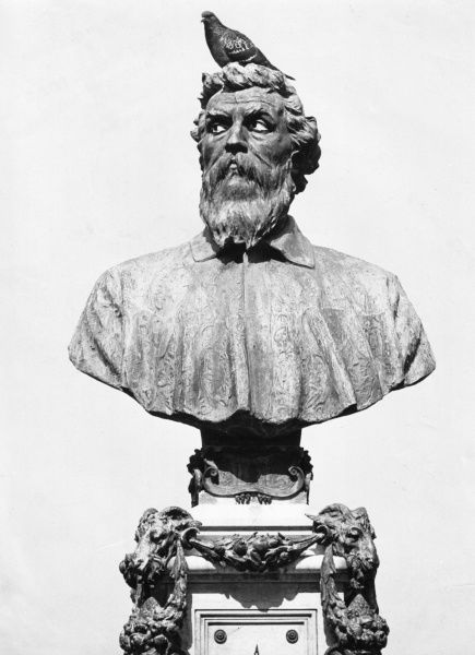 A portrait bust on Benvenuto Cellini (1500-1571), celebrated Italian goldsmith, sculptor, painter, soldier and musician, on the Ponte Vecchio in Florence, Italy, with a pigeon perched on its head