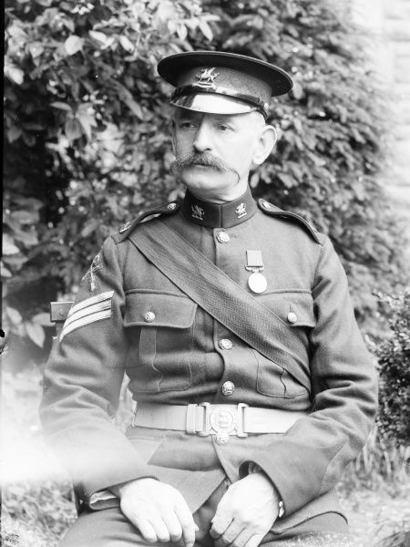 Portrait of a retired army sergeant in full uniform, posing for his photo in a garden, probably in Mid Wales. He wears a medal, and his cap and collar insignia show that he belongs to the Brecknockshire Battalion