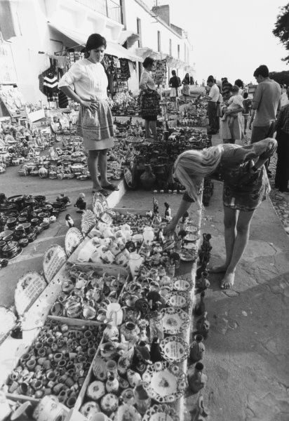 A blonde female tourist picks over some China ornaments for sale on a market stall in Nazare, Portugal. Date: late 1960s