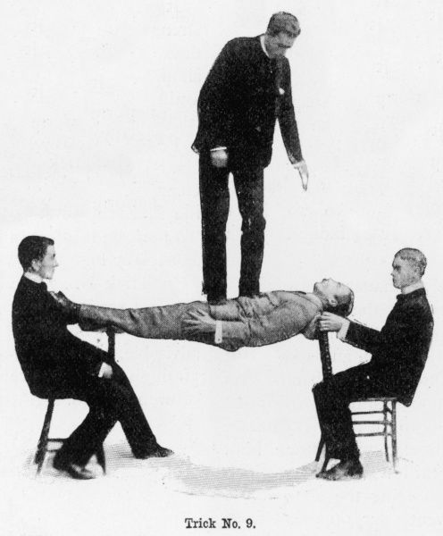 Trick No. 9 - 'How, when lying at length on two chair-backs placed at your extremities, to support a person standing on your chest' from 'How to Pose as a Strong Man' an article by Edward William Barton-Wright in Pearson's Magazine