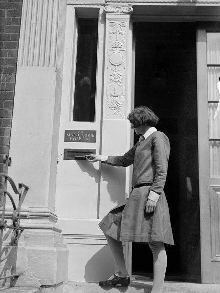 A woman posts a letter into the letter box of the Marie Curie Hospital, Paris, France. Date: early 1930s