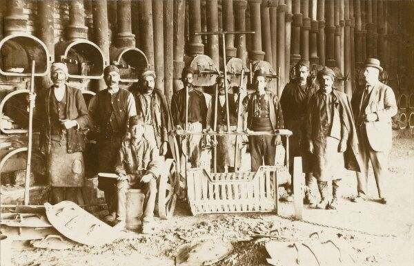 Workers (and the manager or owner - at right) in a Turkish pottery and sand-casting factory
